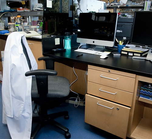 Empty lab coat draped over a chair